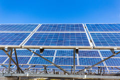 Metal frames with rows of blue solar collectors and sky Stock Photo