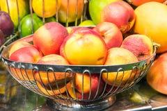 Metal fruit bowl full of peaches Stock Photos