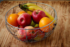 Metal fruit bowl on a wooden surface. Close. Bananas, oranges and apples Royalty Free Stock Images