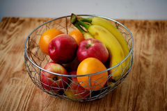 Metal fruit bowl on a wooden surface. Close. Bananas, oranges and apples Stock Image