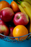 Metal fruit bowl on a wooden surface. Close. Bananas, oranges and apples Royalty Free Stock Photos