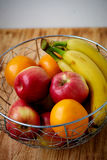 Metal fruit bowl on a wooden surface. Close. Bananas, oranges and apples Stock Images