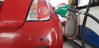 Metal fuel handle inside the gas tank of mini sport car filling gasoline in self service station stock photo