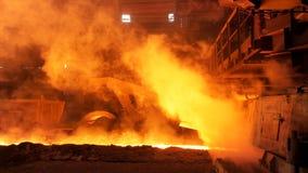 Metal fundido que fluye en canal inclinado en la fábrica rodeada por los clubs del vapor Cantidad común Industria y metalúrgico p fotos de archivo