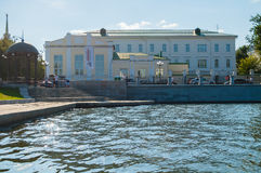 Metal furniture and building of gymnasium built in 1847 along the embankment of the Iset river in Yekaterinburg, Russia. YEKATERINBURG, RUSSIA - AUGUST 24, 2013 Stock Image