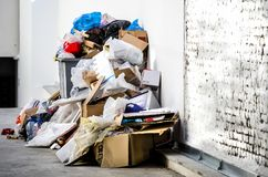 Metal garbage dumpster can overflow and surrounded with litter polluting the street in the city. Metal garbage dumpster can overflow and surrounded with litter Royalty Free Stock Image