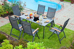 Metal Garden furniture. The metal Garden furniture by the house and the pool Royalty Free Stock Images