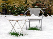 Metal garden furniture ovber the snow. In backyard Royalty Free Stock Image