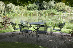 Metal garden furniture at water. Green park with metal chairs and table garden furniture Stock Image
