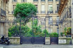 Metal gate of apartments Saint Germain-Luxembourg. Paris, France - June 4, 2017: Forged fence with gate and wicket of Apartment Saint Germain-Luxembourg is royalty free stock photography