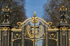 Metal gate decorated with golden ornaments. Metal gate of a park decorated with golden ornaments stock photos