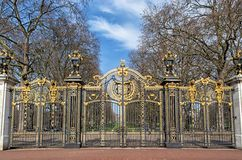 Metal gate decorated with golden ornaments. Metal gate of a park decorated with golden ornaments stock image