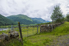 Metal gate and drystone wall Royalty Free Stock Photography