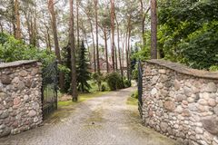 Metal gate open to a cobblestone driveway to a luxurious summer. Villa with brick facade in the forest royalty free stock photo