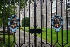 Metal gate to St Patrick cathedral grounds. Metal bar gate with colorful coats of arms from grounds of St Patrick cathedral in Dublin in Ireland Royalty Free Stock Images
