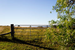 Metal gate and wooden fence post on field on hill royalty free stock images