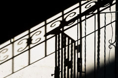 Metal gates with shadow on wall Royalty Free Stock Image