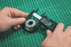 Metal gear measurement process. Factory man, worker measuring steel detail, gear with digital Vernier Caliper at workshop on. Cutting mat, metrology, quality royalty free stock photo