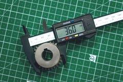 Metal gear measurement process. Measuring steel detail, gear with digital Vernier Caliper at workshop on cutting mat. Metrology, quality, engineer, material stock images