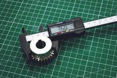 Metal gear measurement process. Measuring steel detail, gear with digital Vernier Caliper at workshop on cutting mat. Metrology, quality, engineer, material stock image