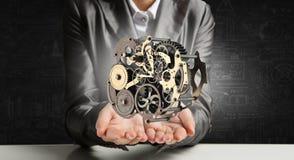 Cogwheel mechanism in hand. Mixed media. Metal gear mechanism in palm. Mixed media Stock Photography