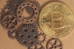 Metal gear wheels with bitcoin. Metal gears wheels with bitcoin on a copper background Royalty Free Stock Image