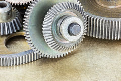 Metal gears and cogwheels on scratched brass background Royalty Free Stock Photo