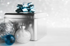 Metal gift box with blue bow and xmas baubles on white glitter background. Merry christmas card. Winter holidays. Xmas theme. Happy New Year Royalty Free Stock Photography
