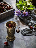 Metal glass with cherry,box with sweet cherry on dark blue background. Royalty Free Stock Photo