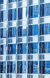 Metal glass facade blue colour of skyscraper. Fragment of the modern building. Many windows pattern.  Royalty Free Stock Images