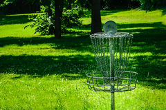 Metal golf basket. Frisbee golf basket with metal chains and basket in green grass with trees Stock Photos