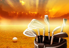 Metal golf club set in leather bag and golf ball on sunrise background Stock Photography