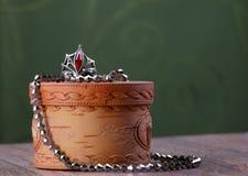 Metal gotas y un anillo con una piedra roja en el pequeño ataúd de la corteza de abedul Imagen de archivo