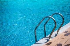 Metal grab bar ladder in blue water swimming pool. Royalty Free Stock Photos