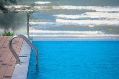 Metal grab bar ladder in blue water swimming pool with sea wave background. Royalty Free Stock Photos