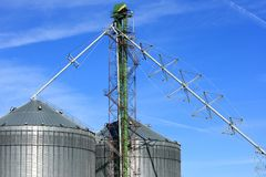 Metal Grain Bins Against A Blue Sky Stock Image