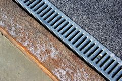 Metal grate of rainwater drainage system on a sidewalk. In wintertime Royalty Free Stock Photography