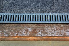 Metal grate of rainwater drainage system on a sidewalk. In wintertime Stock Photos