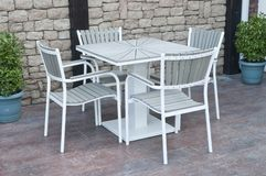 Metal and gray wood outdoor patio furniture for dining. In front of stone wall stock image