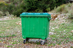 Metal green garbage. Can with wheels in countryside Royalty Free Stock Photo