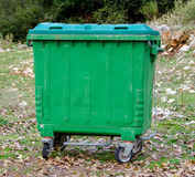 Metal green garbage can with wheels in countryside. Metal green garbage can with wheels in countryside Royalty Free Stock Image