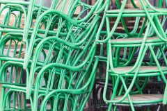 Metal green painted chairs with wooden sits piled outdoor next t stock images