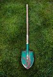 Metal green shovel with wooden handle on grass lawn Stock Images