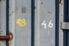 Metal grey old door background with numbers of houses. 48 46 worn and aged Royalty Free Stock Images