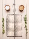 Metal grid for cooking with rosemary and spices on  white rustic background, place for text Stock Images
