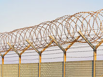 Metal grid fence with loops of  Concertina razor wire and barbed wire Royalty Free Stock Images