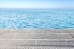 Metal grid floor and blue water background. Royalty Free Stock Photography