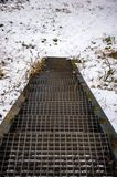 Metal grid stairs. Leading to ground with snow Stock Photo