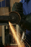 Metal Grinder. Metalworker cutting steel with an angle grinder in a factory Stock Photos