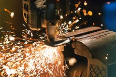 Metal grinder with sparkles in workshop Stock Photo